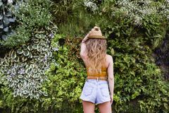 Portrait of a young blonde beautiful woman at the street smiling. Green vegetation background. Lifestyle outdoors. Summertime royalty free stock photos