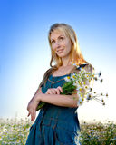 Portrait of the young blonde with a bouquet of wild flowers against the blue sky Stock Photography