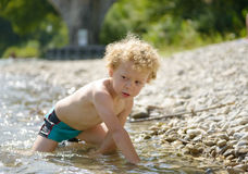 Portrait of a young blonde boy playing in water. Portrait of a young blonde boy playing in the river Royalty Free Stock Photo