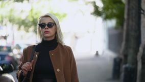 Portrait of young blonde businesswoman goes to work or date in autumn city. Girl have stylish look, sunglasses and nose stock video
