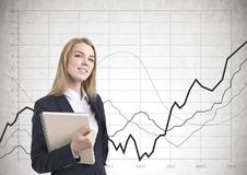 Smiling businesswoman with notebook, graphs Stock Photography