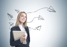 Smiling businesswoman with notebook, paper planes Royalty Free Stock Photography