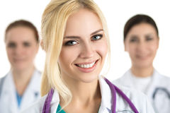 Portrait of young blonde female doctor surrounded by medical tea Stock Images
