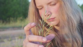 Portrait of the young blonde girl 11 years old. Pensively and dreamily looks at the blade of grass.