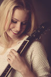 Portrait of young blonde guitar player woman Stock Photography