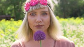Portrait of a young blonde hippie woman with nose ring and magenta pink flower band in hair holding onion violet flower