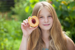 Portrait of a young blonde little girl with peach Stock Photo