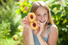 Portrait of a young blonde little girl with peach Royalty Free Stock Images