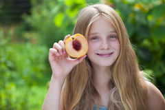Portrait of a young blonde little girl with peach Stock Photography