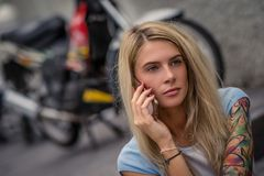 Portrait of young blonde sitting on the background of the motorcycle. Talking on the phone. Female hands with a tattoo royalty free stock image