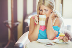 Portrait of a young blonde, sitting in a cafe Stock Photography
