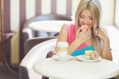 Portrait of a young blonde, sitting in a cafe Stock Image