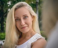 Portrait of a young blonde in a white blouse and flowing hair, sitting in the garden with a beautiful girlfriend stock photos