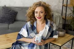 Portrait of young blonde woman at bright living room drinking cup of tea or coffee royalty free stock photos