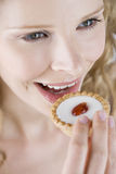 A portrait of a young blonde woman eating a cake with a cherry on top, close-up Stock Photography