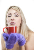 Portrait of the young blonde woman in fluffy mittens with a mug Royalty Free Stock Photos