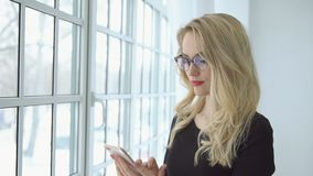 Portrait of a young blonde woman in glasses with a phone at the big window stock video footage