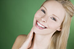 A portrait of a young blonde woman with her hand on her neck, smiling Royalty Free Stock Photography