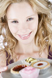 A portrait of a young blonde woman holding a plate of assorted cakes Stock Photography
