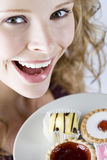A portrait of a young blonde woman holding a plate of assorted cakes, close-up Royalty Free Stock Images