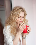 Portrait of a young blonde woman holding a red mug wearing a white shirt with an expression of being sadness. Fair hair  female Royalty Free Stock Photo