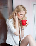Portrait of a young blonde woman holding a red mug wearing a white shirt with an expression of being sadness. Fair hair  female Stock Images