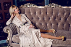 Portrait of young blonde woman. Lying on the sofa in a long dress Stock Photo