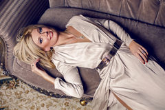Portrait of young blonde woman. Lying on the sofa in a long dress Stock Photography