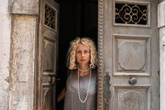 A portrait of a young blonde woman in a neutral gray dress, standing in a doorway of a shabby door. Stock Images