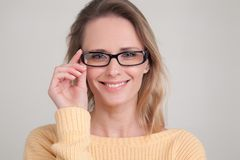 Portrait of young blonde woman with peaceful face expression standing against white background keeping her fingers on glasses and royalty free stock photography