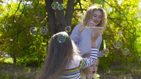 Portrait of young blonde woman staying in the sunny park and blowing soap bubbles. Her two little pretty daughters. Running around trying to catch bubbles stock footage
