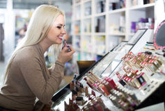 Portrait of  young blondie selecting lipstick in store Stock Photos