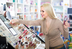 Portrait of  young blondie selecting lipstick in store. Portrait of smiling young american  blondie selecting lipstick in store Stock Photography