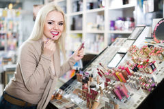 Portrait of  young blondie selecting lipstick in store Royalty Free Stock Image