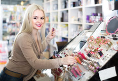 Portrait of  young blondie selecting lipstick in store. Portrait of smiling young russian blondie selecting lipstick in store Stock Photos