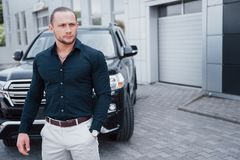 Portrait of a young bodyguard near the car. He performs dangerous work stock images