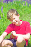 Portrait of young boy. Sitting on spring meadow stock photo