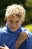 Portrait of a young boy. Young blond boy wrapped in a blue towel Royalty Free Stock Image