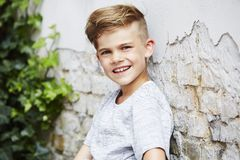 Portrait of a young boy against brick wall Royalty Free Stock Image