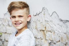 Portrait of a young boy against brick wall Stock Photo