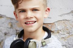 Portrait of a young boy against brick wall Stock Image