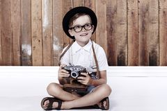 Portrait of a young boy against bwooden wall Stock Photo
