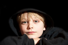 Portrait of young boy aged nine years. Portrait of young handscome boy on black background wearing black hooded top royalty free stock photography