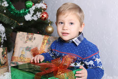 Portrait of a young boy behind the child a Christmas tree. The boy is holding a New Year green gift with orange bow. A child in winter blue sweater. On sweater Royalty Free Stock Image