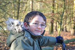 Portrait of young boy on bike in woods. Wearing winter clothes Stock Photography