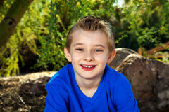 Portrait Of Young Boy In Blue. Outdoor portrait of a young boy in blue.  He is smiling and looks approachable Stock Photography