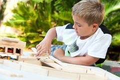 Boy building structure with wooden blocks. Portrait of young boy building structure with wooden blocks outdoors Royalty Free Stock Photo