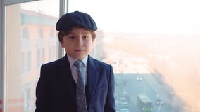 Portrait young boy in business suit straightens tie and cap in business office stock video footage