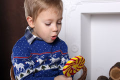 Portrait of a young boy with a delicious large colorful lollipop. A child in winter blue sweater. On sweater ornament deer white. Blond Stock Photos