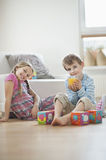 Portrait of young boy drinking orange juice while sitting with sister on floor Stock Photography